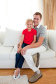 Blond little girl sitting on sofa with her father — Stock Photo