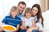 Portrait of a smiling family eating crisps while watching TV — Stock Photo