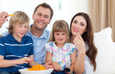 Happy family eating crisps — Stock Photo