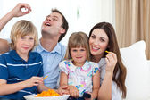 Young family eating crisps while watching TV — Stock Photo