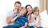 Happy family singing a karaoke together — Stock Photo
