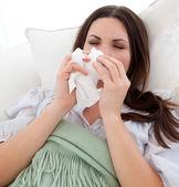 Young sick woman lying on the sofa — Stock Photo
