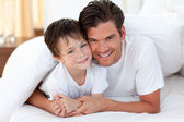 Smiling father and his son lying on bed — Stock Photo