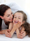 Little girl and her mother having fun on bed — Stock Photo