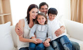 Portrait of a smiling family sitting on the sofa — Stock Photo