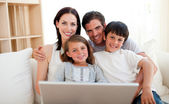 Happy family surfing the internet — Stock Photo