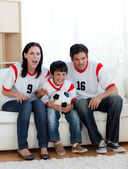 Parents and their son watching a football match — Stock Photo