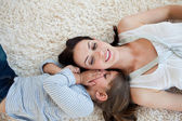 Smiling mother and her daughter lying on the floor — Stock Photo