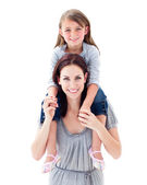 Young mother giving her daughter piggyback ride — Stock Photo