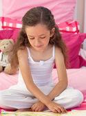 かわいい女の子のベッドの上を読んで — ストック写真