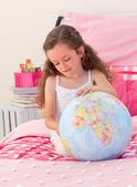 Little girl having fun with a terrestrial globe — Stock Photo