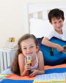 Close-up of a cute girl girl singing and her brother playing gui — Stock Photo