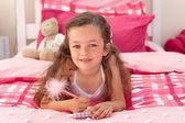 Carina ragazza sdraiata sul letto — Foto Stock