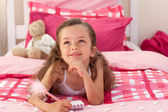 Smiling girl writing on bed — Stock Photo