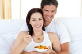 Happy couple eating fruits lying on their bed — Stock Photo