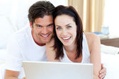 Smiling couple using a laptop lying on their bed — Stock Photo