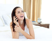 Radiant woman on phone lying on her bed — Stock Photo