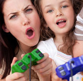 Excited mother and her daughter playing video games — Stock Photo
