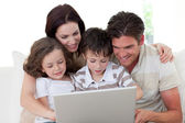 Family using a laptop on the sofa — Stock Photo