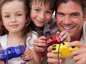 Happy father and his children playing video games — Stock Photo
