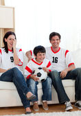 Positive family watching football match — Stock Photo