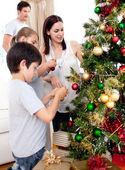 šťastné děti a rodiče, zdobení vánočního stromku — Stock fotografie