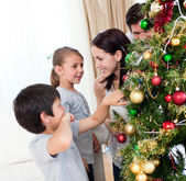 Smiling family decorating a Christmas tree with boubles — Stock Photo