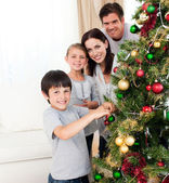 Smiling family decorating a Christmas tree — Stock Photo