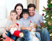 Portrait of a smiling family at Christmas time holding lots of p — Stock Photo