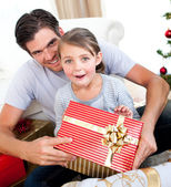 Surprised little girl opening a Christmas present with her fathe — Stock Photo