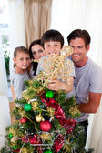 Happy family decorating a Christmas tree — Stock Photo
