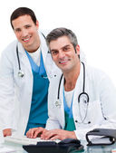 Two handsome male doctors working at a computer — Stock Photo