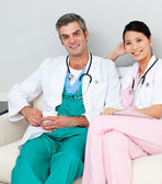 Smiling doctors relaxing and drinking coffee — Stock Photo