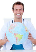 Portrait of a smiling male doctor holding a terrestrial globe — Stock Photo