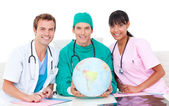 Joyful medical team looking at terrestrial globe — Stock Photo
