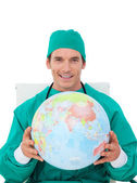 Confident doctor holding terrestrial globe — Stock Photo