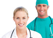 Blond female doctor and smiling surgeon — Stock Photo