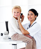 Smiling female doctor checking her patient's ears — Stock Photo