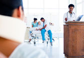 Injured woman sitting on wheelchair and a medical team at work — Stock Photo