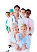 Attentive medical team taking care of a senior woman and her gra — Stock Photo