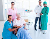 Attentive medical team taking care of a senior woman — Stock Photo
