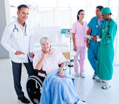 Positive medical team taking care of a senior woman — Stock Photo