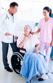 Smiling medical team taking care of a senior woman — Stock Photo