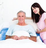 Smiling nurse fixing a senior patient's bed — Stock Photo