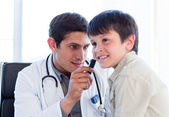 Serious doctor examining little boy's ears — Stock Photo