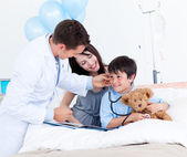 Charming doctor playing with a little boy and his mother — Stock Photo