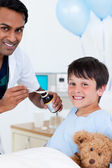 Smiling doctor examining a little boy with his father — Foto Stock