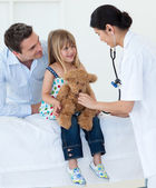 A doctor examining smiling child and playing with a teddy bear — Stock Photo