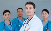 Young male Doctor with his team in the background — Stock Photo