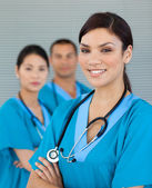 Attractive female doctor with his colleagues in the background — Stock Photo